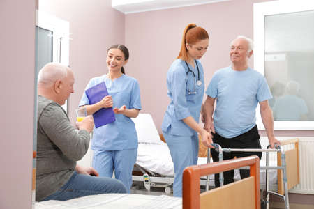 Nurses with senior patients in hospital ward. Medical assisting Stock Photo