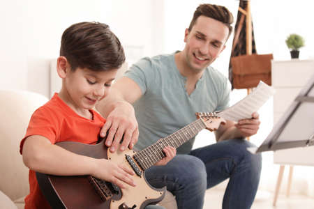 Little boy playing guitar with his teacher at music lesson. Learning notes