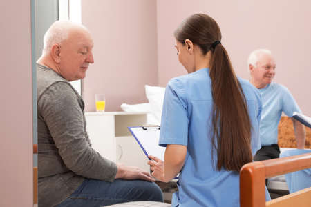Nurse talking with senior patient in hospital ward. Medical assisting