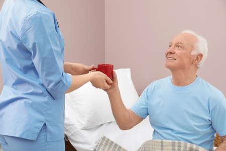 Nurse giving drink to senior man in hospital ward. Medical assisting