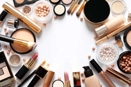 Diferentes productos de maquillaje de lujo sobre fondo blanco, vista superior. Espacio para texto