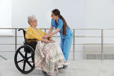 Nurse covering senior woman in wheelchair with plaid at hospital. Medical assisting Stock Photo
