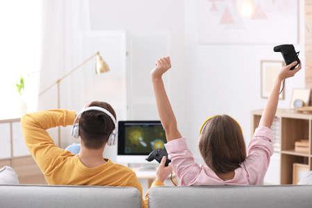 Jeune couple émotif jouant à des jeux vidéo à la maison