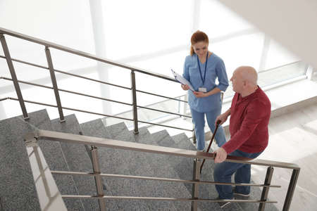 Nurse assisting senior man with cane to go up stairs indoors