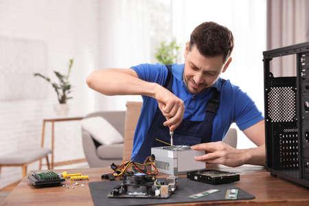 Mannelijke technicus die voedingseenheid aan tafel binnenshuis repareert Stockfoto