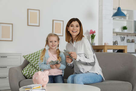 Mother and daughter counting money on sofa indoors Standard-Bild