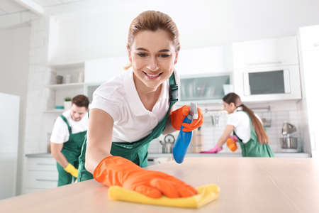 Woman using rag and sprayer for cleaning table with colleagues in kitchen