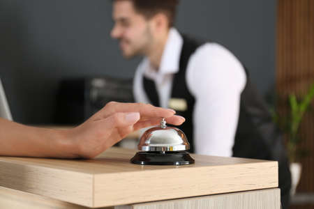 Woman ringing in bell on reception desk, closeup Stockfoto