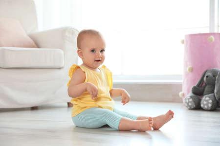 Cute baby girl sitting on floor in room Stock fotó
