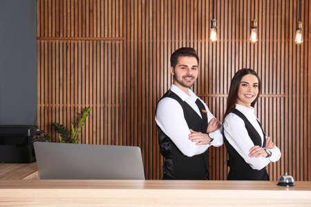 Lächelnde Empfangsdamen am Schreibtisch in der modernen Lobby Standard-Bild
