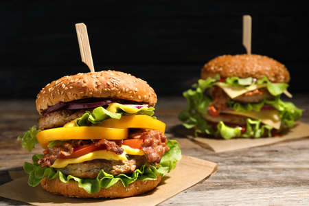 Tasty burgers with bacon on table. Space for text
