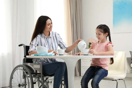 Mother in wheelchair and her daughter drinking tea at table indoors Imagens