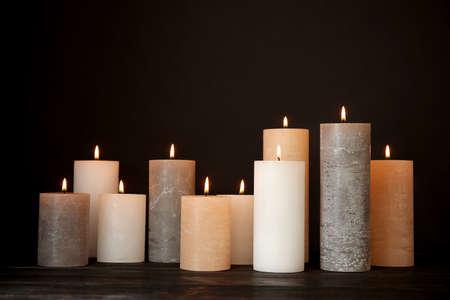 Alight wax candles on table against dark background Reklamní fotografie