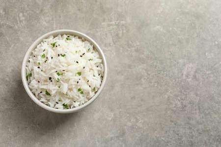 Bol de riz cuit savoureux sur fond gris, vue de dessus. Espace pour le texte Banque d'images