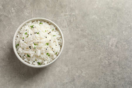 Bowl of tasty cooked rice on grey background, top view. Space for text Imagens
