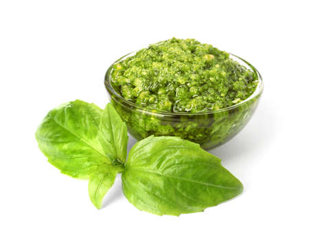 Bowl of tasty pesto sauce with basil leaves isolated on white