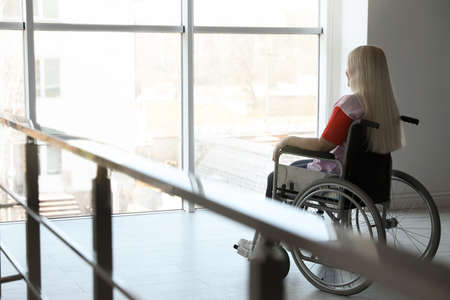 Mature woman sitting in wheelchair near window at home