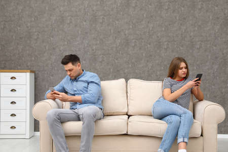 Couple engaged in smartphones while spending time together at home. Loneliness concept Banco de Imagens