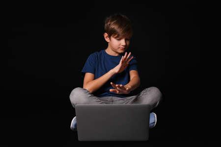 Scared child with laptop on black background. Danger of internet