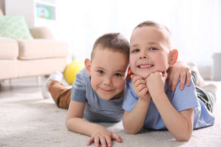 Portrait of cute twin brothers on floor in living room