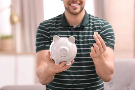 Man with piggy bank and money at home