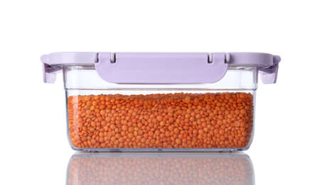 Box with uncooked lentils on white background