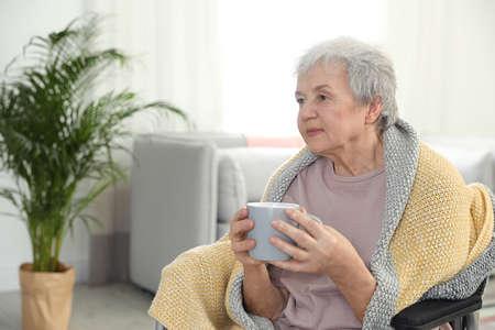 Donna anziana coperta di coperta che beve tè a casa di cura, spazio per il testo. Assistere le persone anziane Archivio Fotografico