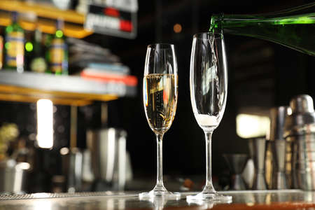 Pouring champagne from bottle into glass on counter in bar. Space for text Stock Photo
