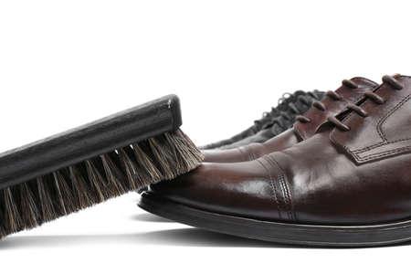 Stylish men's shoes and cleaning brush on white background, closeup Stock Photo