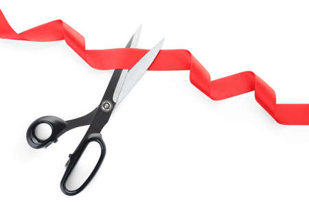 Stylish scissors and red ribbon on white background. Ceremonial tape cutting Фото со стока