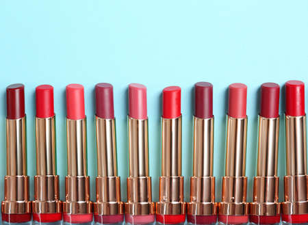 Flat lay composition with different stylish lipsticks on color background