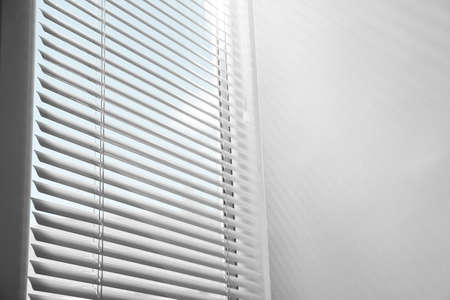 Window with closed horizontal blinds indoors, low angle view. Space for text