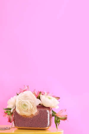 Elegant handbag with spring flowers on table against pink background, space for text