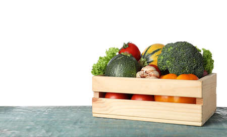 Wooden crate full of delicious fresh vegetables on table against white background