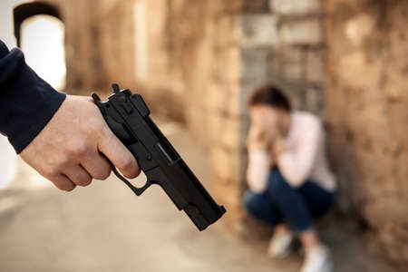Armed man holding woman hostage outdoors, focus on hand with gun. Criminal offence 版權商用圖片