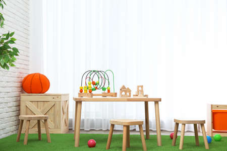 Stylish playroom interior with toys and modern wooden furniture 免版税图像