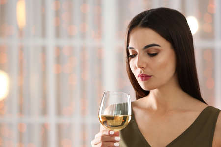 Beautiful young woman with glass of luxury white wine indoors. Space for text