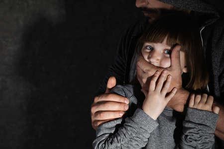 Hombre adulto que cubre la boca de la niña asustada, espacio para texto. Niño en peligro