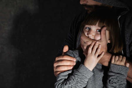 Homme adulte couvrant la bouche d'une petite fille effrayée, espace pour le texte. Enfant en danger