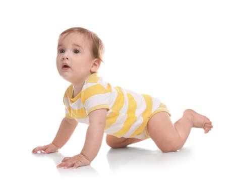 Lindo bebé gateando sobre fondo blanco. Foto de archivo