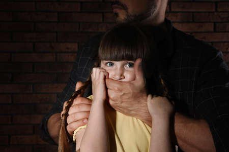 Adult man covering scared little girl's mouth near brick wall, closeup. Child in danger