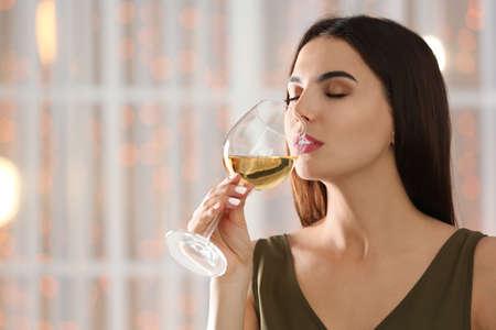 Hermosa mujer joven con copa de vino blanco de lujo en el interior. Espacio para texto