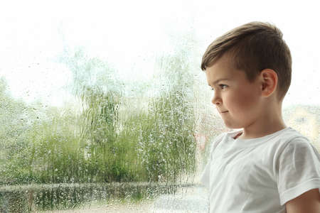 Cute little boy near window indoors, space for text. Rainy day Foto de archivo