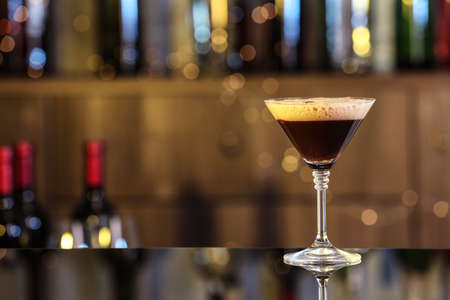 Glass of delicious Espresso Martini on bar counter, space for text. Alcohol cocktail