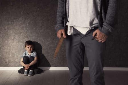Uomo con pantaloni decompressi e ragazzino spaventato al chiuso. Bambino in pericolo