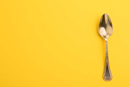 Clean tea spoon and space for text on color background, top view