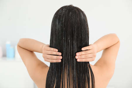 Frau, die Haarspülung im hellen Badezimmer anwendet Standard-Bild