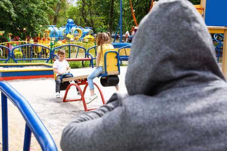 Suspicious adult man spying on kids at playground, space for text. Child in danger Stock Photo