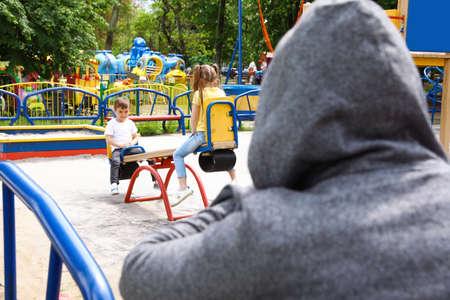 Verdächtiger erwachsener Mann, der Kinder auf dem Spielplatz ausspioniert, Platz für Text. Kind in Gefahr Standard-Bild