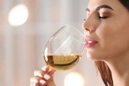Beautiful young woman with glass of luxury white wine indoors, closeup view. Space for text Banco de Imagens